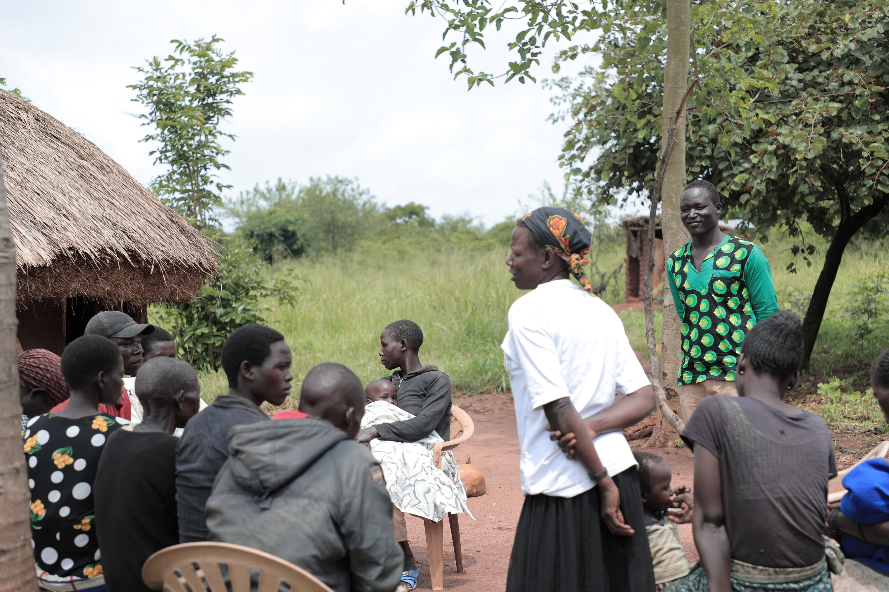 Photo of a group of Ugandans engaging in a workshop with a health worker.