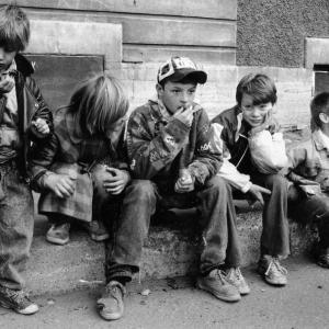 A group of teens and children sitting on a curb
