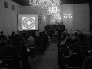 Photo of people sitting at a presentation featuring the Doctors of the World logo