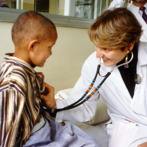A woman examining a young girl with shaved head using a stethoscope