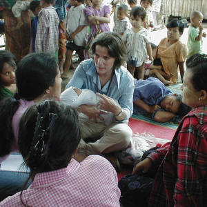 Dr. Victoria Sharp sitting on the floor holding a baby, surrounded by women and children