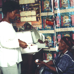A young woman is standing, talking to an older woman who is sitting