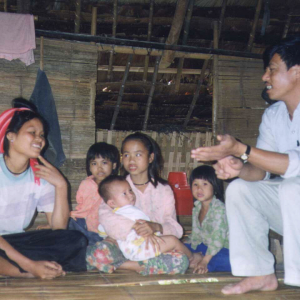 A man is kneeling in front of a family while explaining something