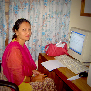 A women dressed in traditional Nepali clothes sitting in front of an old PC