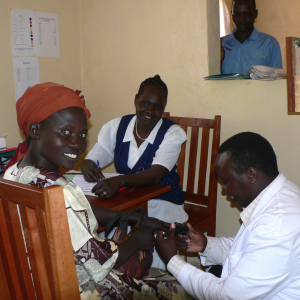 A woman is smiling at the camera while a physician is reading her blood oxygen level and two healthcare workers are looking on