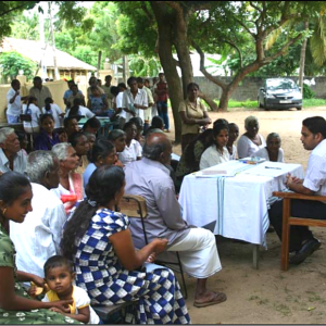 A community health volunteer is sitting at a table, addressing a crowd of about 40 people in a health education session