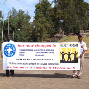 Two men are holding a large banner announcing the celebration ceremony of Doctors of the World changing its name to HealthRight International