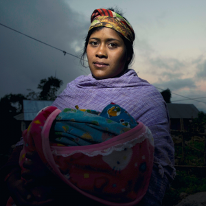 A woman in Nepali dress is holding a swaddled baby and looking at the camera