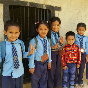 A group of Nepali schoolchildren in uniforms are smiling at the camera