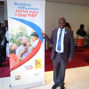 """A man is pointing at a banner reading """"Revitalizing HIV prevention, HIV Self testing & Oral PrEP"""""""