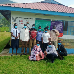 A group of healthcare workers wearing face masks are standing in front of a medical center in Kenya